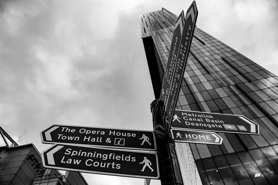 The standard black and white photo of road signage in on Deansgate in Manchester, UK, right in front of the Beetham Tower. Digital and print photography by Ian Philip Thompson.
