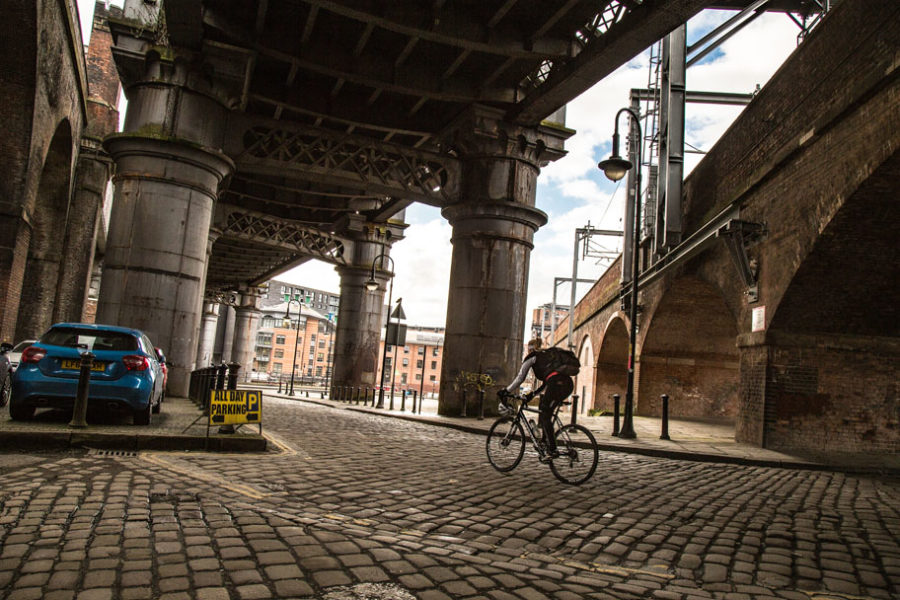 A cyclist rips along the cobblestones in the Castlefield neighbourhood in Manchester, UK underneath the Great Northern Viaduct, a historical relic of Manchester.