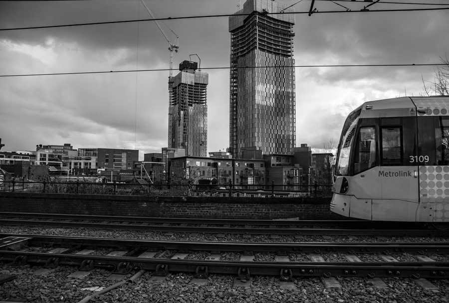 A black and white view of the under construction towers in Manchester, UK from the Deansgate Station, with a tram in the view just for fun.